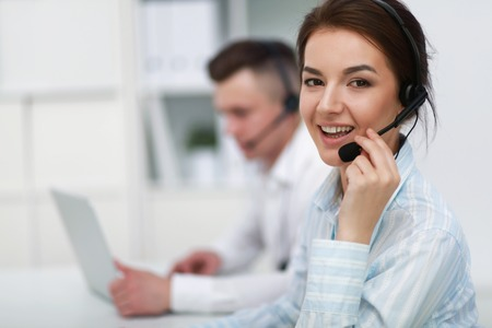 personal call: Businesswoman with headset smiling at camera in call center
