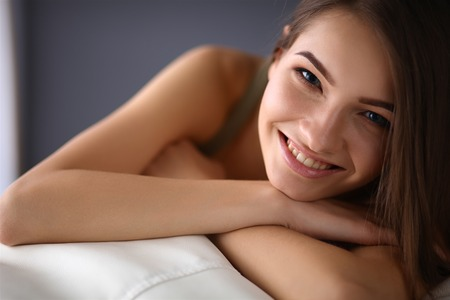 Closeup of a smiling young woman lying on couch Stock Photo