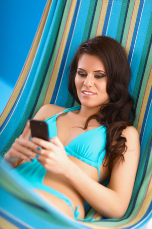 Relaxed young woman looking at mobile phone in hammock photo