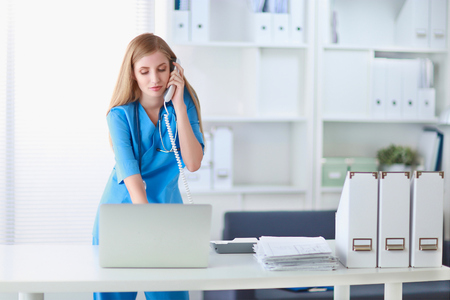 Medical doctor woman with computer and telephone. Stock Photo