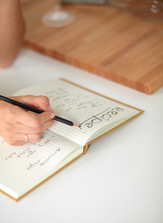 Happy beautiful woman standing in her kitchen writing on a notebook at home photo
