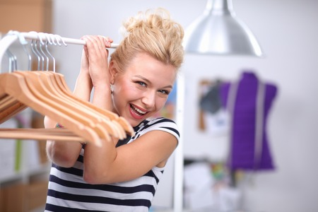 Beautiful young stylist near rack with hangers photo