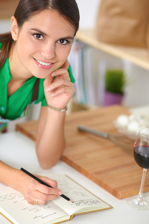 Happy beautiful woman standing in her kitchen writing on a note photo