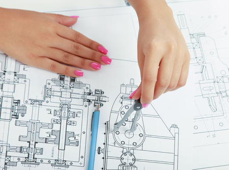 Female architect working with blueprints at office desk photo