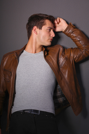 Man posing in leather jacket near wall