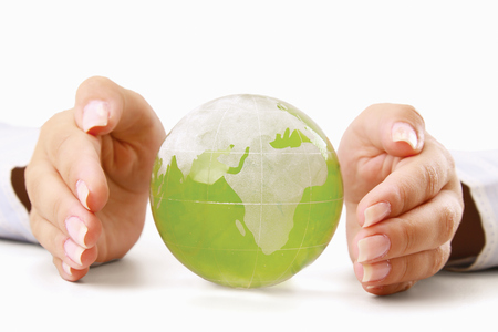 Hands holding a green earth, isolated on white background photo