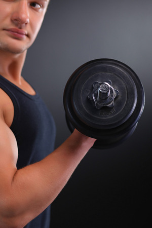 powerfully: Fit muscular man exercising with dumbbell