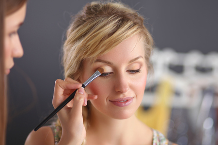 Artist doing professional make up of woman photo