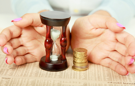 Female hand's with hourglass and coin photo