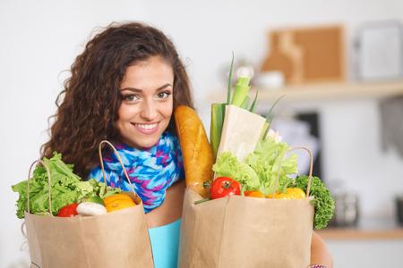 Mujer joven que sostiene el bolso de compras de comestibles con las verduras De pie en la cocina. Foto de archivo - 33045045