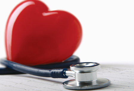 Medical stethoscope and heart isolated on white. photo