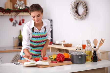 Jonge vrouw lezing kookboek in de keuken, op zoek naar recept