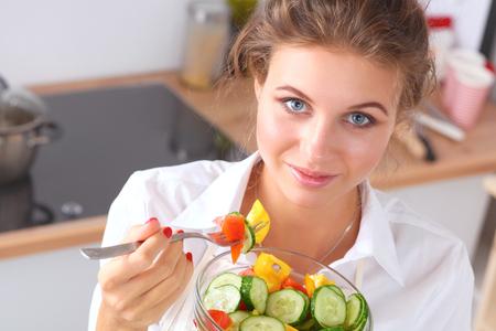 モダンなキッチンに新鮮なサラダを食べる若い女性 写真素材