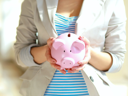 white piggy bank: Young beautiful woman standing with piggy bank (money box).