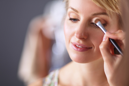 Artist doing professional make up of woman Stock Photo