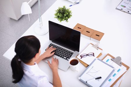 professional portrait: Portrait of a businesswoman sitting at a desk with a laptop, isolated