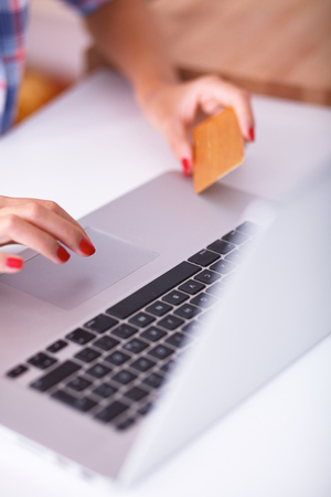 house shopping: Smiling woman online shopping using computer and credit card in kitchen Stock Photo