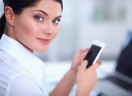 message sending: Businesswoman sending message with smartphone sitting in the office