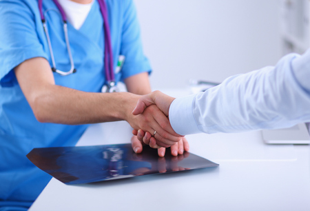 happy customer: Doctor shaking hands with a patient, sitting on the desk