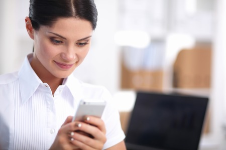 25 years old: Businesswoman sending message with smartphone sitting in the office