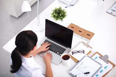 Portrait d'une femme d'affaires assis à un bureau avec un ordinateur portable, isolé Banque d'images