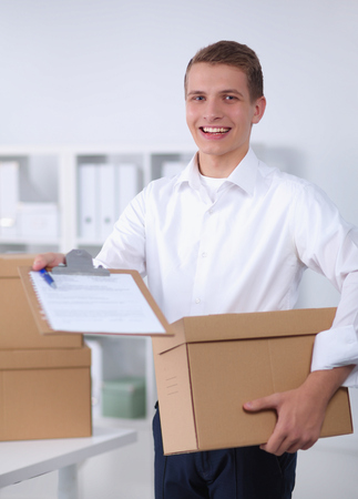 Delivery man with  parcel and a tablet standing in office Stock Photo