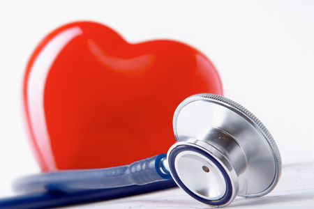 clinical research: A heart with a stethoscope lying Stock Photo