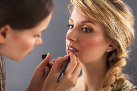 Artist doing professional make up of woman Stock Photo - 34553615