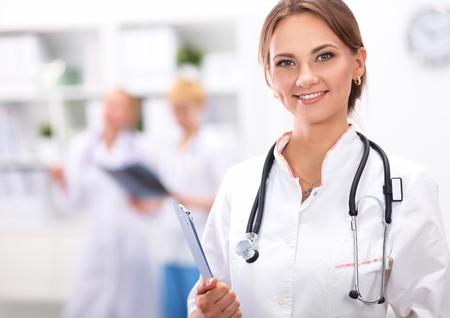 doctor: Mujer m�dico de pie con la carpeta en el hospital