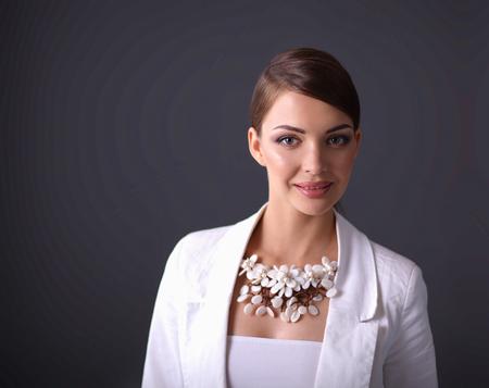 mujer elegante: Retrato de mujer joven con perlas, aislado sobre fondo gris Foto de archivo