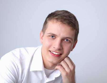 estilo urbano: Retrato de hombre joven y sonriente sentado sobre fondo gris