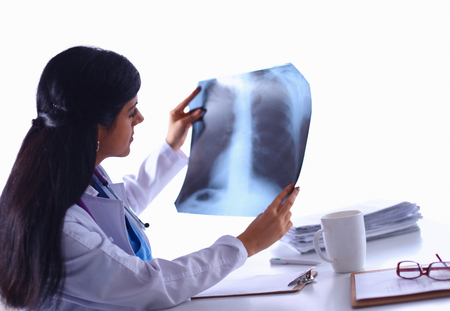 Young female doctor studying x-ray image, sitting at the desk photo
