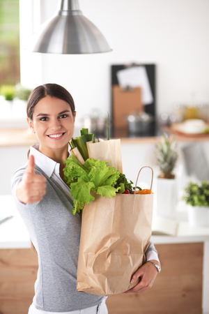 paper bag: Young woman holding grocery shopping bag with vegetables and showing ok Stock Photo