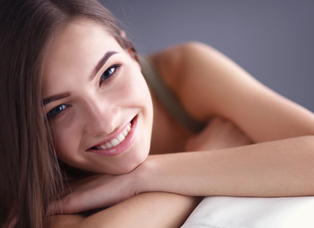Closeup of a smiling young woman lying on couch at home Stock Photo