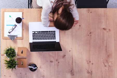 Young woman sleeping on laptop in the workplace photo