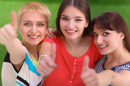 Three girls friends gesturing thumbs up photo