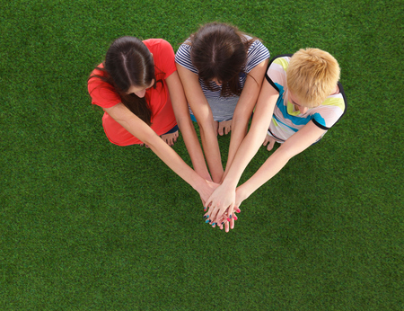unanimous: People joining their hands  standing on green grass Stock Photo