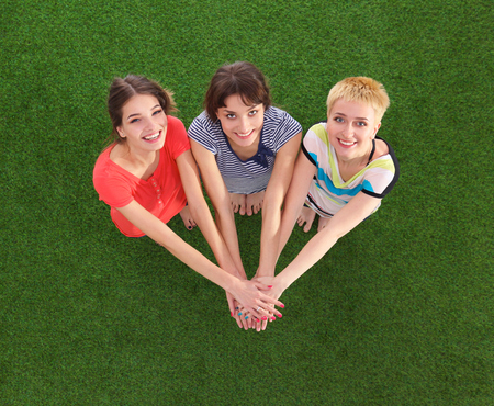 joining: People joining their hands  standing on green grass Stock Photo