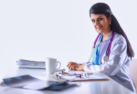 Female doctor sitting on the desk with paper  and working photo