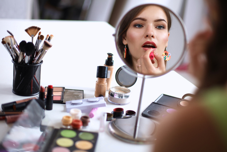 Young beautiful woman making make-up near mirror,sitting at the desk