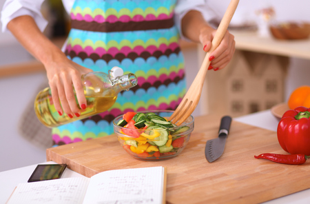 healthy product: Smiling young woman mixing fresh salad Stock Photo
