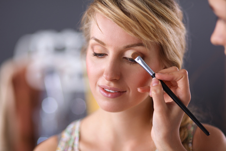 make up artist: Artist doing professional make up of woman Stock Photo