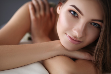 home comforts: Closeup of a smiling young woman lying on couch at home Stock Photo