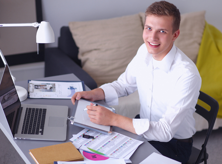 young office workers: Young businessman working in office, standing near desk Stock Photo