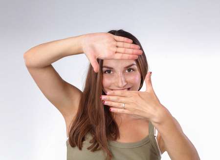 Young attractive woman framing her hands Stock Photo