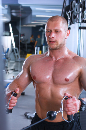 Young man training at gym with exercises photo