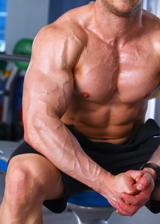 smiing: Young handsome man sits after workout in the gym