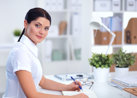 gleeful: Attractive businesswoman sitting  on desk in the office Stock Photo