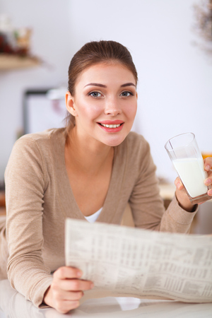 house robes: Happy young woman having healthy breakfast in kitchen Stock Photo