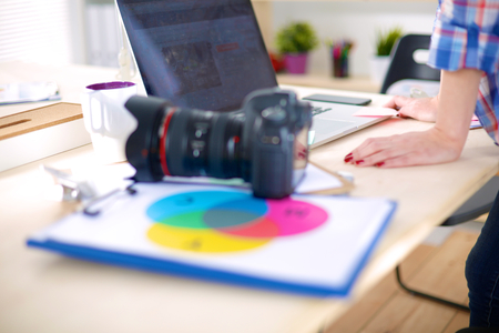 Female photographer sitting on the desk with laptop Archivio Fotografico
